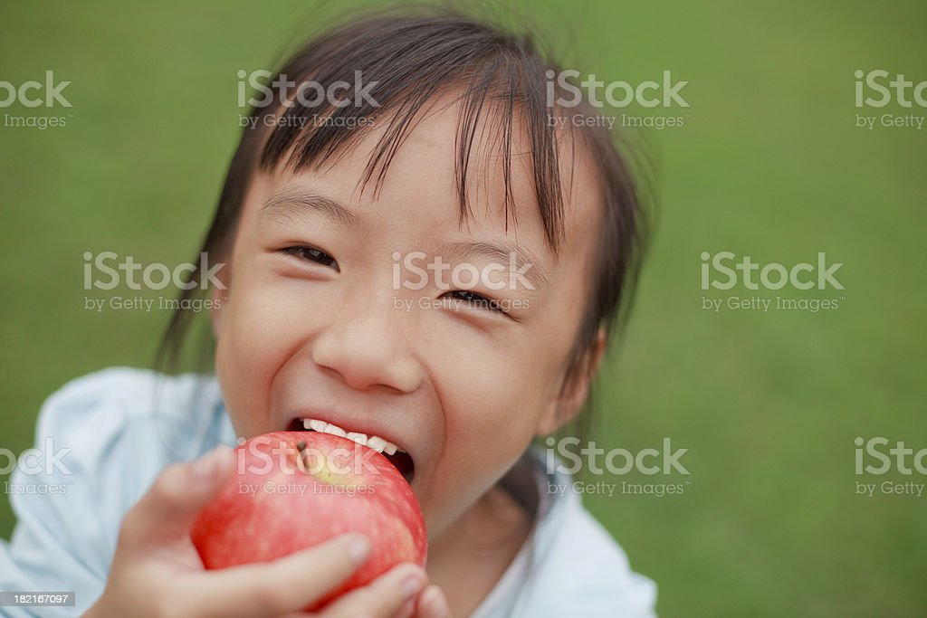 Cute Little Asian Girl Eating Apple royalty-free stock photo