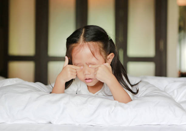 Cute little asian girl in lying on a bed rubs eyes. stock photo
