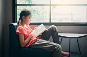 istock Cute little Asian girl reading a book in the living room at home, Education and knowledge concept 1183349245