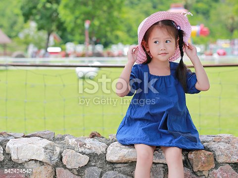 429922edc21 istock Cute little asian girl wear straw hat sitting on the stone wall  against green public