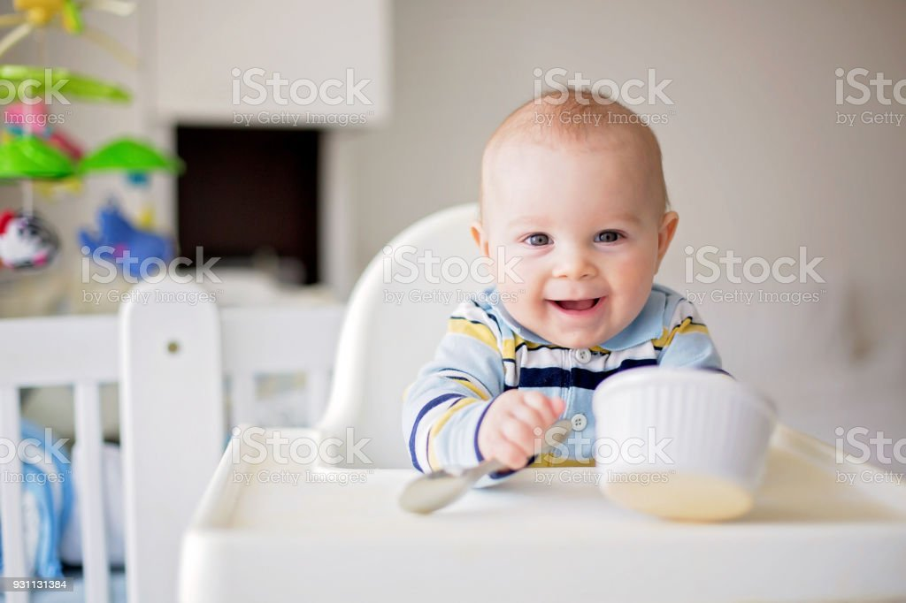 Cute little baby boy, eating mashed vegetables for lunch, mom feeding him stock photo