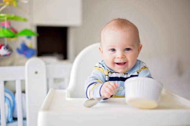Bebê menino bonitinho, comer purê de legumes para o almoço, mãe alimentá-lo - foto de acervo