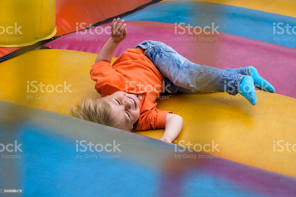 Cute little baby boy happily playing on bouncy castle stock photo