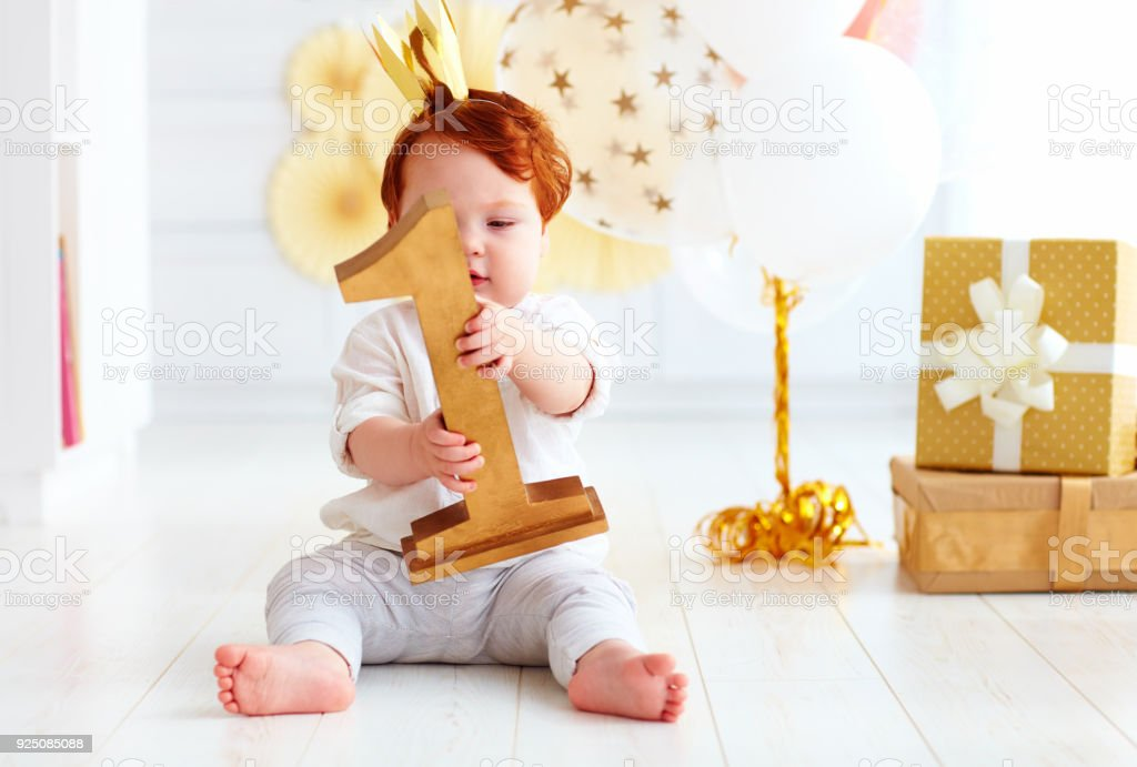 cute little baby boy holding number one, while sitting on party background stock photo