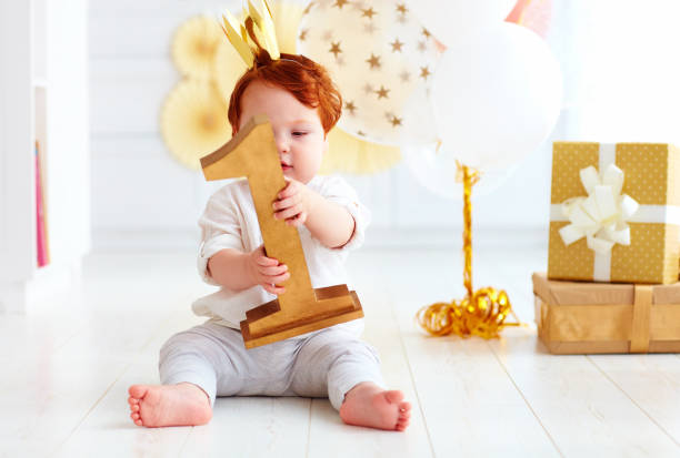 cute little baby boy holding number one, while sitting on party background cute little baby boy holding number one, while sitting on party background first birthday stock pictures, royalty-free photos & images