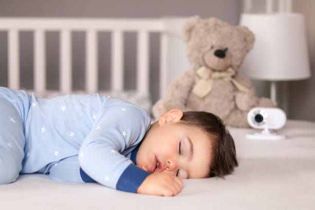 Cute little baby boy in light blue pajamas sleeping peacefully on bed at home with baby monitor camera and soft teddy bear toy at background. Child daytime sleeping schedule stock photo