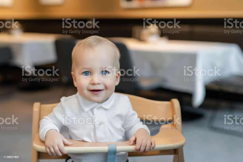 Cute Little Baby Boy In White Polo Tshirt Sitting In Wooden Baby