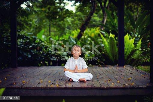 istock cute little baby boy, kid meditating in rainy forest park, sitting on wooden decks 922701452