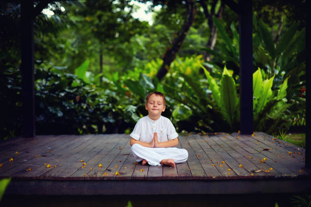 cute little baby boy, kid meditating in rainy forest park, sitting on wooden decks stock photo
