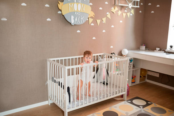 cute little baby boy looking out of his bed - playpen stock pictures, royalty-free photos & images