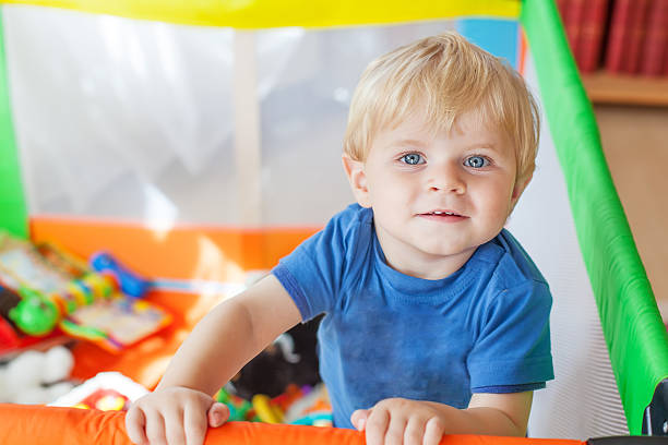 cute little baby boy playing in colorful playpen, indoors - playpen stock pictures, royalty-free photos & images