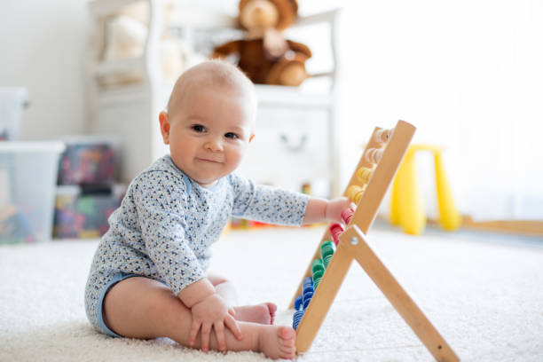 Cute little baby boy, playing with abacus at home Cute little baby boy, playing with abacus at home, sunny kids room child prodigy stock pictures, royalty-free photos & images