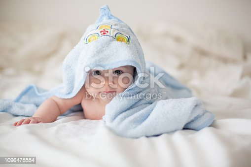 923852236 istock photo Cute little baby boy, relaxing in bed after bath, smiling happily 1096475554