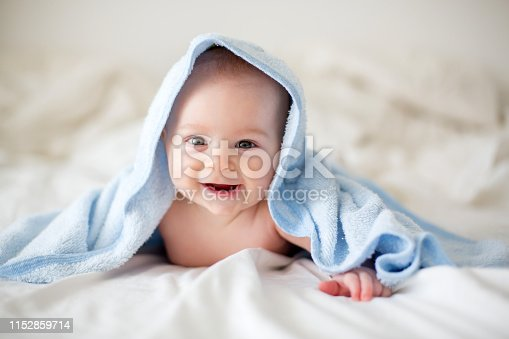 923852236 istock photo Cute little baby boy, relaxing in bed after bath, smiling happily 1152859714