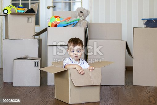 istock Cute little baby boy sitting inside cardboard box with big boxes full of toys on background, moving out concept 999080008