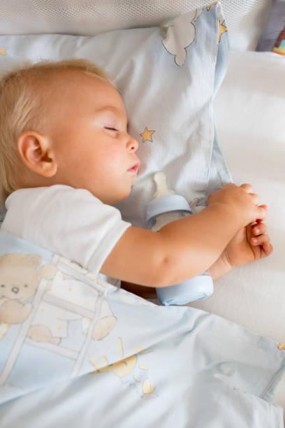 Lindo bebé niño, dormir con biberón con leche de fórmula - foto de stock