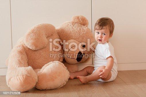 istock Cute little baby boy with big teddy bear 1021212328