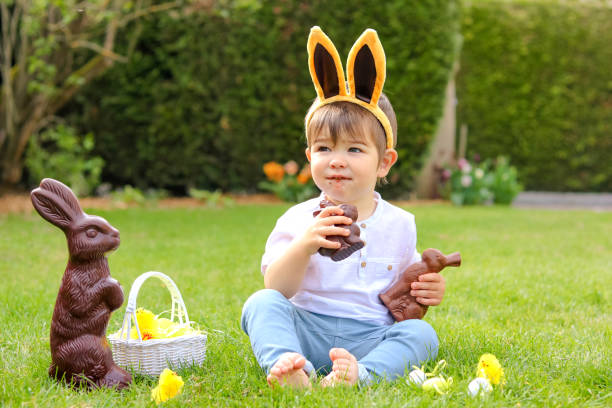Cute little baby boy with bunny ears eating chocolate Easter bunnies sitting on green grass outside in the spring garden with basket of easter eggs and big chocolate rabbit. Happy sweet childhood stock photo