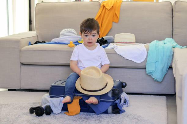 niedlicher kleiner junge mit lustigen gesichtsausdruck hält hut in den händen sitzen auf gepackten koffer mit kleidung ragen bereit für den urlaub. reisen mit kinder-konzept. verpackung für urlaub. - küstenfamilienzimmer stock-fotos und bilder
