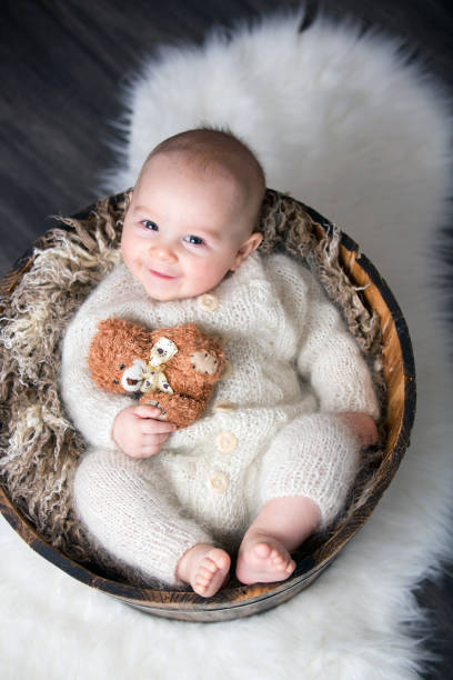Cute little baby boy with handmade knitted cloths, playing with little teddy bear toy Cute little baby boy with handmade knitted cloths, playing with little teddy bear toy, smiling at camera bib overalls boy stock pictures, royalty-free photos & images