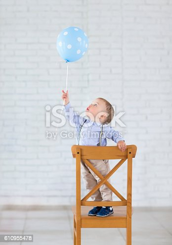 istock Cute little baby boy with one balloon 610955478