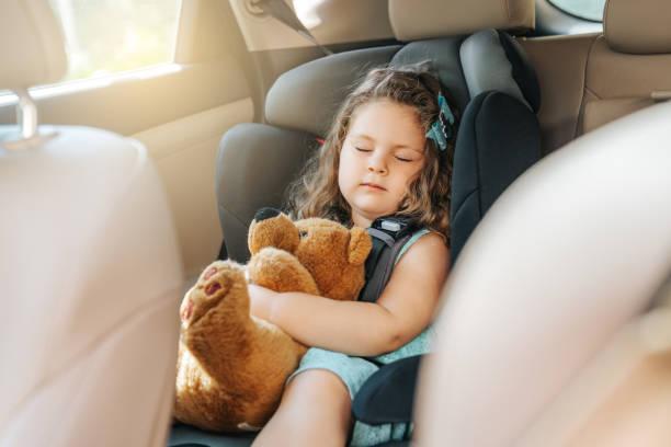 petit enfant mignon de chéri s'asseyant dans le siège d'auto. verticale du petit enfant mignon de chéri s'asseyant dans le siège d'auto. concept de sécurité. - child car sleep photos et images de collection
