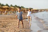 Beautiful children having fun on a sandy beach. Kids enjoying summer sunny day playing and running over the beach