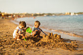 Beautiful children building castle on a sandy beach. Kids enjoying summer sunny day playing with toys