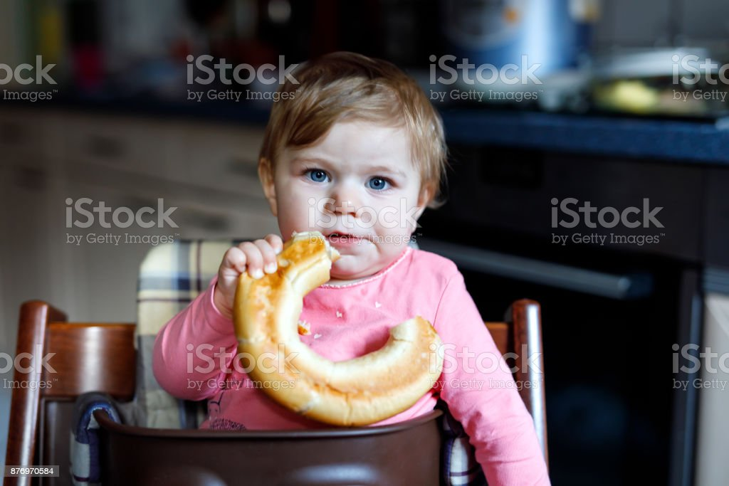 Cute little baby girl eating bread. Child eating for the first time piece of pretzel. stock photo