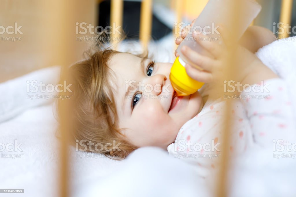 Cute little baby girl holding bottle with formula mild and drinking. Child in baby cot bed before sleeping stock photo