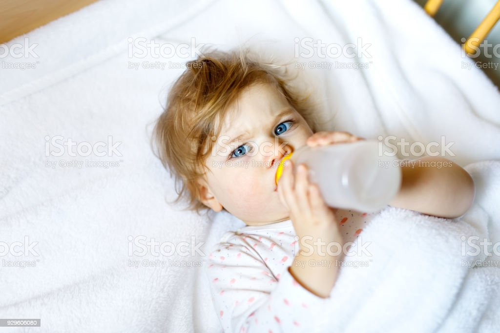 Cute little baby girl holding bottle with formula milk and drinking. Child in baby cot bed before sleeping stock photo
