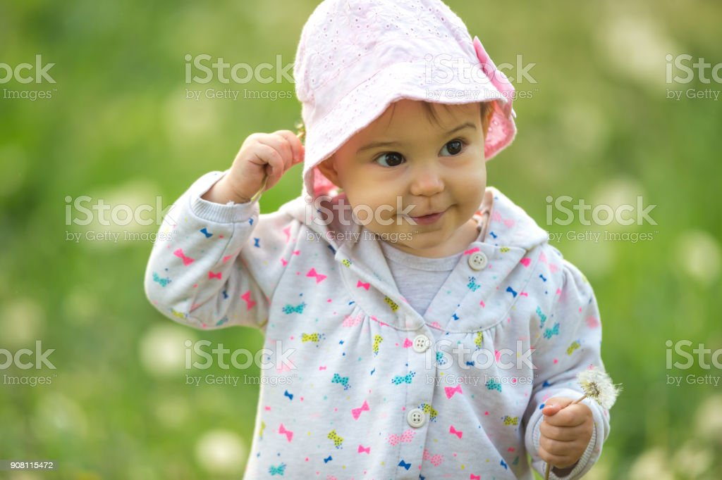 Cute little baby girl holding her hat outdoors stock photo