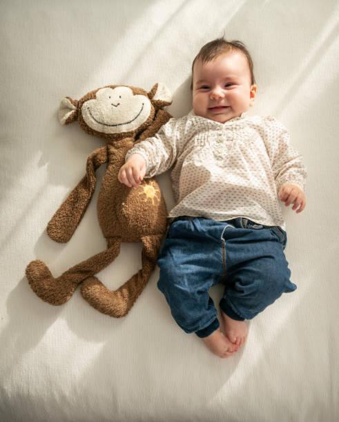 nettes kleines baby mädchen liegt auf sofa neben kuscheltier - kemter stock-fotos und bilder