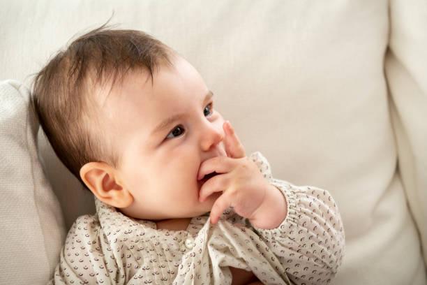 nettes kleines baby mädchen auf dem sofa liegend - kemter stock-fotos und bilder