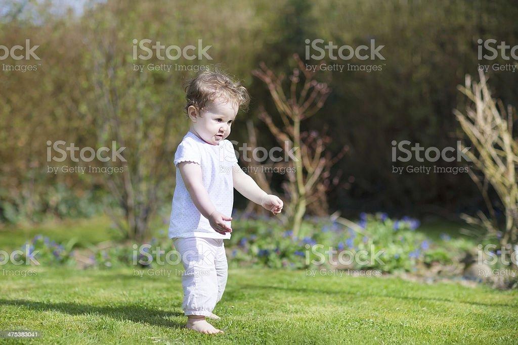 Linda little baby girl que sus primeros pasos en el jardín - Foto de stock de Aire libre libre de derechos