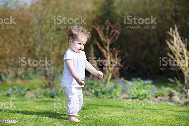 Linda Little Baby Girl Que Sus Primeros Pasos En El Jardín Foto de stock y más banco de imágenes de Aire libre