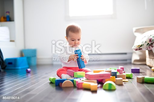istock Cute little baby girl play with plastic bricks sitting indoors on a tiles floor 854518014