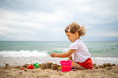 Beautiful baby girl building castle on a sandy beach