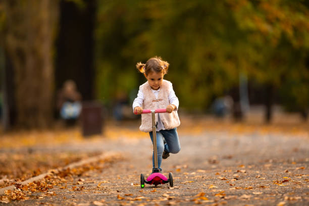 Cute little baby girl rides on a kick scooter stock photo