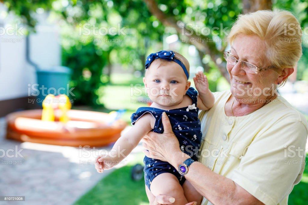 Niedliche kleine Baby-Mädchen mit Großmutter an Sommertag im Garten – Foto