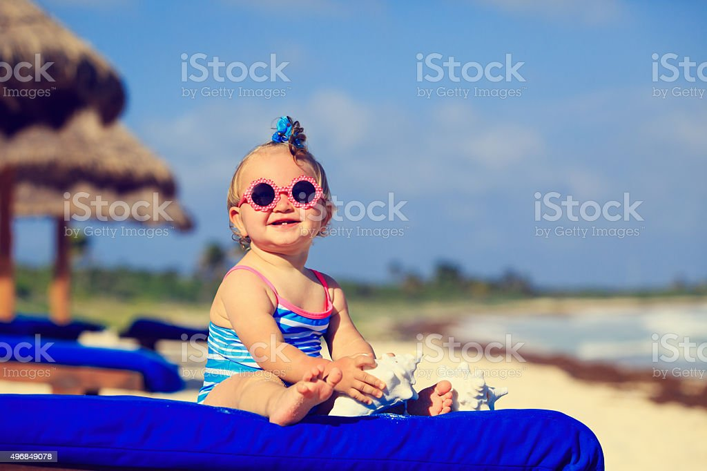 cute little baby girl with seashells on tropical beach stock photo