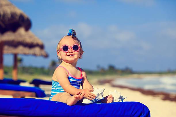 cute little baby girl with seashells on tropical beach stock photo