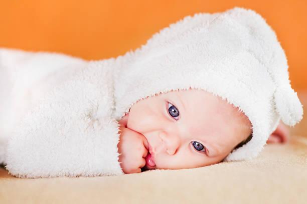 Süße kleine baby liegen und saugen seinen Finger – Foto