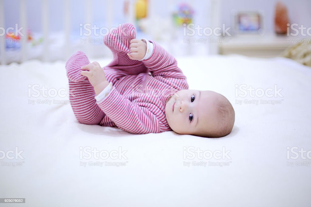 Cute little baby plays with his legs on the bed in bedroom. - foto stock
