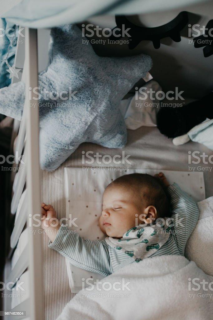 Cute little baby sleeping in Nursery Cot stock photo