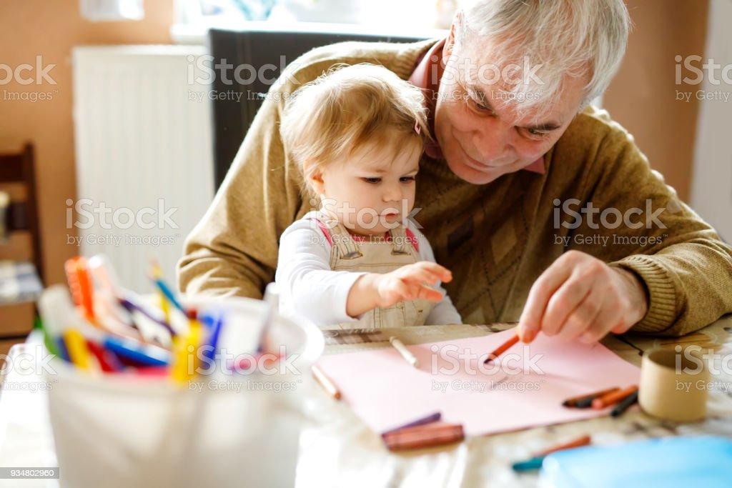 귀여운 작은 아기 유아 소녀와 잘생긴 수석 할아버지 집에서 화려한 연필 그림. 손자와 함께 재미 있는 남자 - 로열티 프리 2명 스톡 사진
