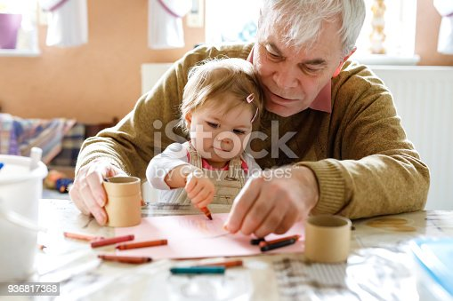 istock Cute little baby toddler girl and handsome senior grandfather painting with colorful pencils at home. Grandchild and man having fun together 936817368