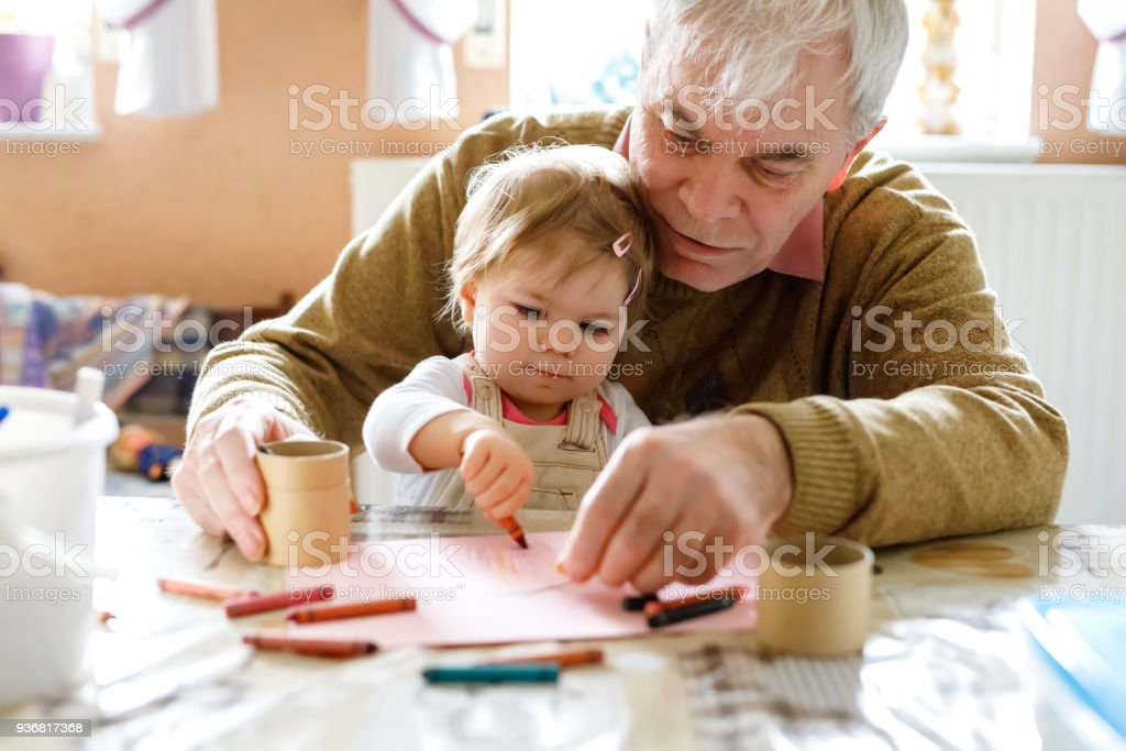 Süße kleine Baby Kleinkind Mädchen und gut aussehend senior Großvater Malerei mit bunten Bleistiften zu Hause. Enkelkind und Man gemeinsam Spaß haben – Foto
