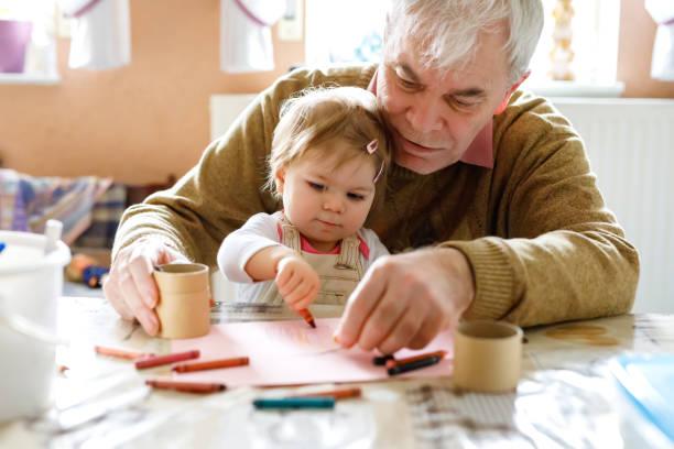 Bebezinho da criança menina e bonito avô sênior, pintando com lápis coloridos em casa. Neto e homem se divertindo juntos - foto de acervo