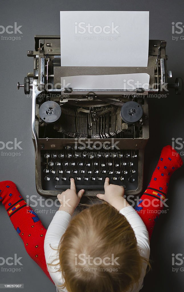 Cute little baby typing on retro typewriter royalty-free stock photo